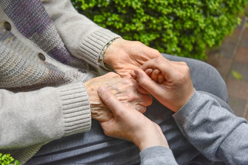 おばあちゃんの手を握りしめる写真