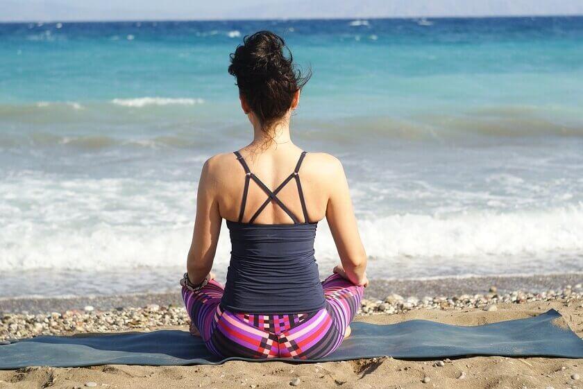 海辺で瞑想する女性