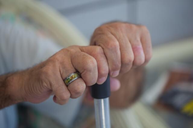 お年寄りの手と杖