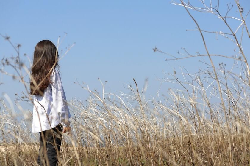 枯れた草原に立つ少女
