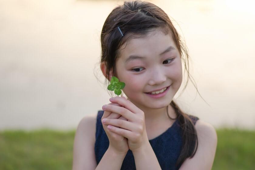 四つ葉のクローバーを見つけた少女