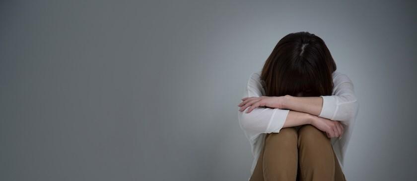 膝を抱え落ち込む女性