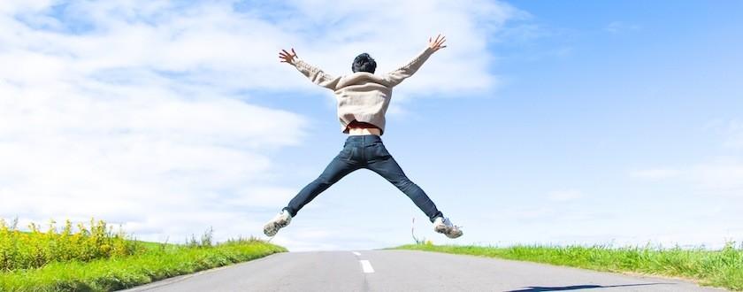 道路の真ん中で大の字に飛び上がる青年